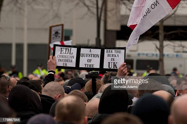CONTENT] A member of the English Defence League holds up a sign asking for the Burka to be banned in the UK at a March in Luton