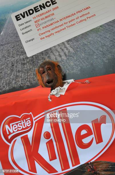 Member of the environmental action group Greenpeace wearing an orangutan mask takes part in an anti-deforestration rally while holding a 'Kit Kat'...