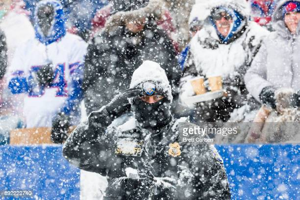 A member of the Erie County Sheriff's department salutes amidst heavy snow as the national anthem plays before the game between the Buffalo Bills and...