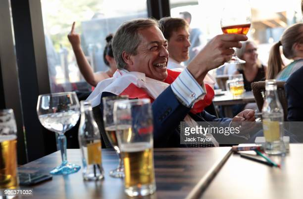 Member of the European Parliament and former Leader of the UK Independence Party Nigel Farage watches England take on Belgium in a World Cup match...