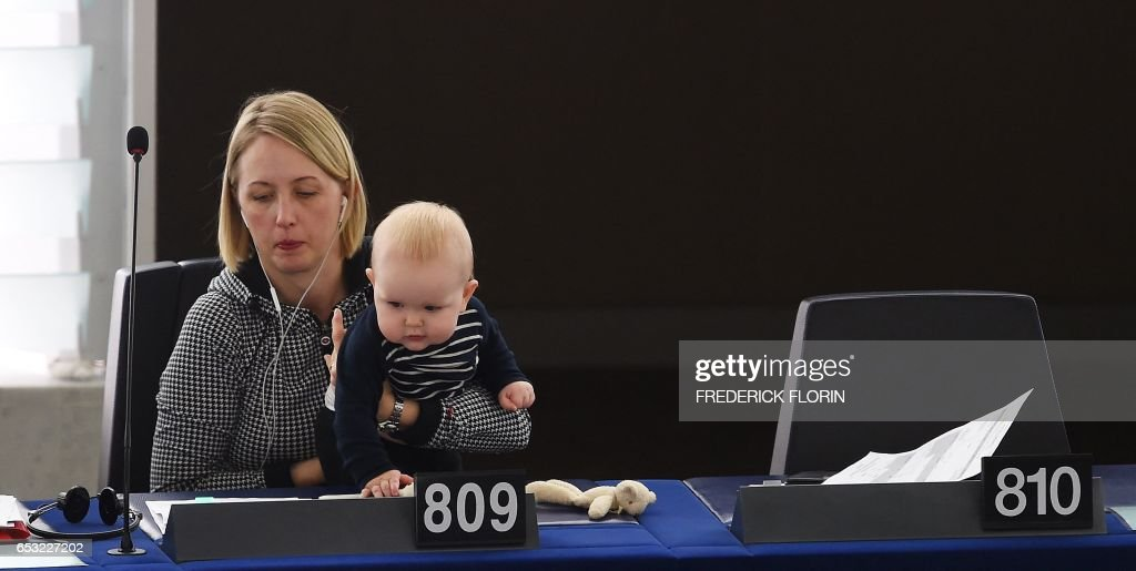 Member of the European Parliament Swedish Jytte Guteland holds her baby as she takes part in a voting session at the European Parliament in Strasbourg, eastern France, on March 14, 2017. /