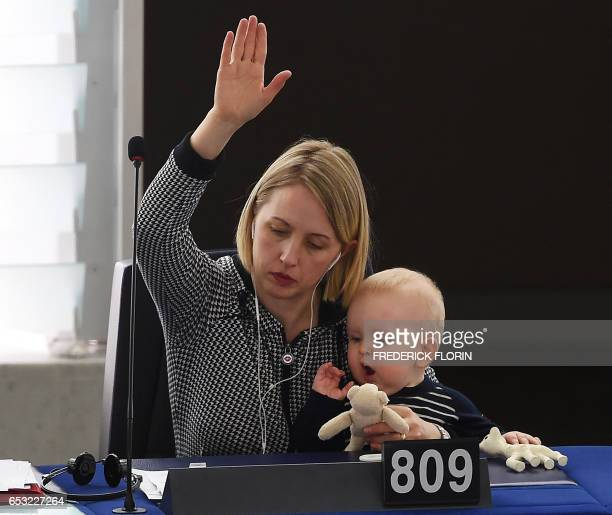 Member of the European Parliament Swedish Jytte Guteland holds her baby as she takes part in a voting session at the European Parliament in...