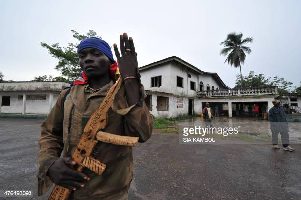 A member of the exSeleka rebels poses with his wooden weapon in front of late Centrafrican emperor JeanBedel Bokassa's palace in Beringo on March 3...