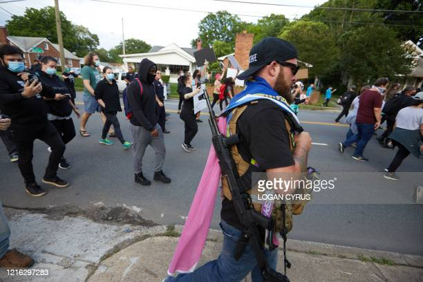 A member of the farright militia Boogaloo Bois walks next to protestors demonstrating outside Charlotte Mecklenburg Police Department Metro Division...