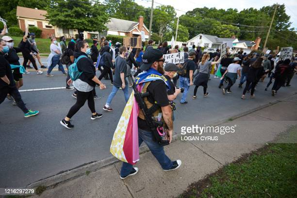 A member of the farright militiaBoogaloo Bois walks next to protestors demonstrating outside Charlotte Mecklenburg Police Department Metro Division 2...