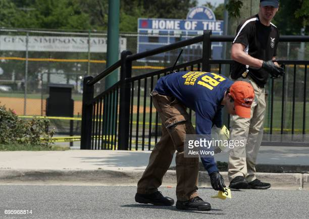 A member of the FBI puts down a marker as he searches for evidence at the scene of this morning's shooting at Eugene Simpson Stadium Park June 14...