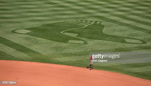 Member of the Fenway Park grounds crew rakes the dirt on the infield before a game between the Boston Red Sox and the Houston Astros at Fenway Park...