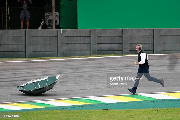 A member of the FIA retrieves an umbrella from the circuit during final practice for the Formula One Grand Prix of Brazil at Autodromo Jose Carlos...