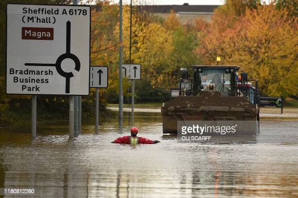 A member of the Fire and rescue service wades through flood water as he escorts a JCB towing an truck along a flooded road Rotherham northern England...