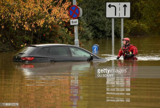Member of the Fire and Rescue service wades through flood water as he passes an abandoned car on a flooded road Rotherham, northern England on...