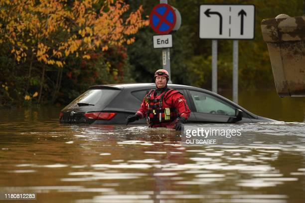 A member of the Fire and Rescue service wades through flood water as he passes an abandoned car on a flooded road Rotherham northern England on...