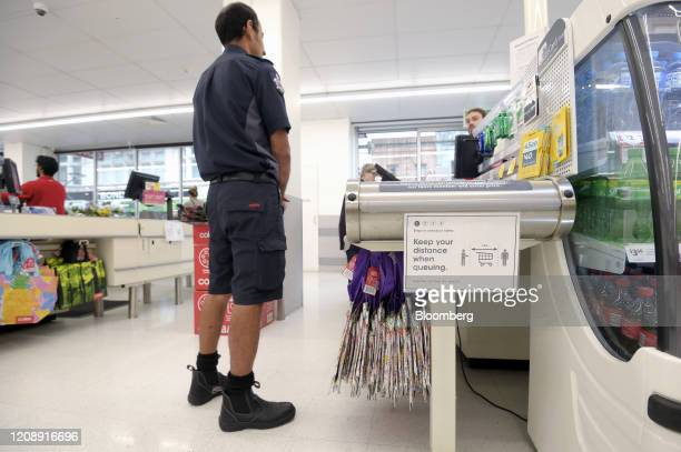 A member of the Fire and Rescue services waits to be served at a checkout during hours designated for prioritizing health care and emergency workers...