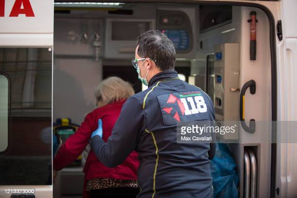 A member of the First Aid Team helps an old woman getting in the ambulance on March 18 2020 in Bologna Italy The Italian government continues to...
