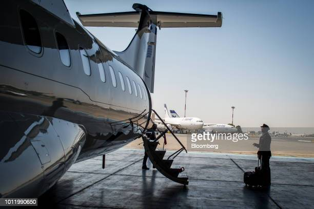 A member of the flight crew stands beside the access stairs of a new twin engine ATR 72600 turboprop aircraft following its arrival at Mehrabad...