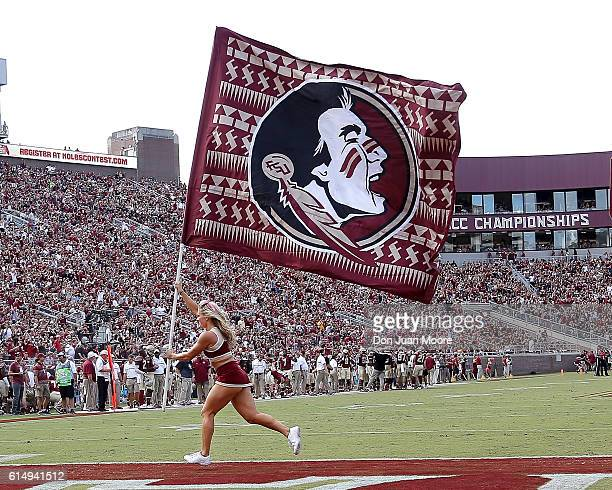 A member of the Florida State Seminoles Cheerleaders runs across the end zone with a flag during the game against the Wake Forest Demon Deacons after...