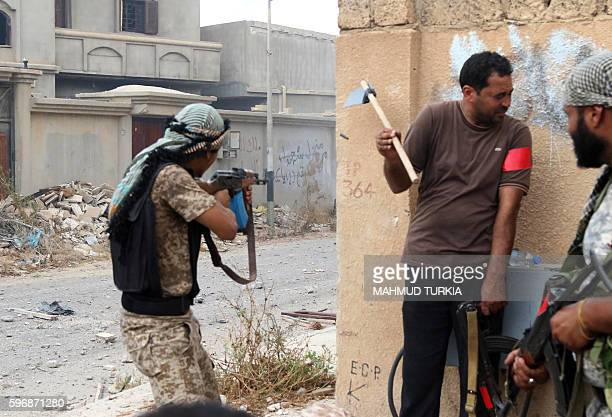 A member of the forces loyal to Libya's UNbacked Government of National Accord fires his rifle as others protect themselves behind a wall on August...