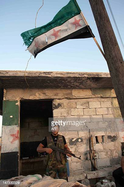 A member of the Free Syria Army stands guard at an outpost on the outskirt of Marea near Aleppo in northern Syria on June 27 2012 International envoy...