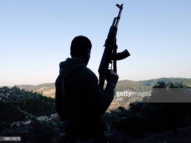A member of the Free Syrian Army looks at the valley in the village of Ain alBaida in the Idlib province of Syria not far from the Turkish border on...