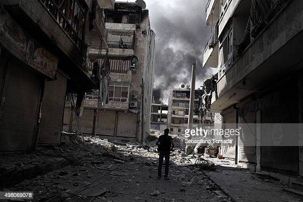 A member of the Free Syrian army observes the damage caused by a week long of fighting with soldiers loyal to Bashar Al Assad's regime along Alarkoub...