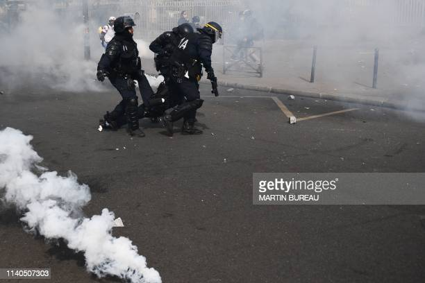 A member of the French antiriot police CRS is evacuated after being injured during clashes with demonstrators on the sidelines of the annual May Day...