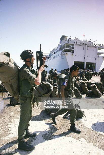 A member of the French Marine contingent of the Multinational Force gets his bags and FAMAS assault rifle ready to load onto the ferry Esterel as he...