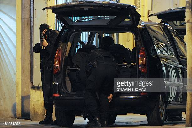 A member of the French police special force GIPN looks down the scope of his rifle as another readies his gear near a jewellery store where two...