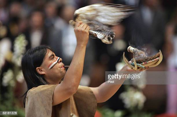A member of the GabrielenoTongva tribe performs during the processional at the interfaith prayer service at the Cathedral of Our Lady Queen of Angels...