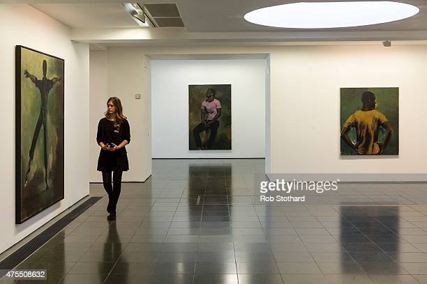 A member of the gallery staff walks past Lynette YiadomBoakye's paintings 'Intersteller' 'Coterie of Questions' and 'The Knowledge Of The East' are...