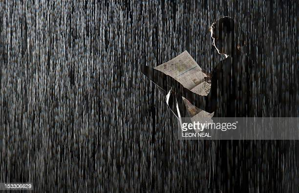 A member of the gallery team poses with a newspaper inside a temporarily dry area of the 'Rain Room' installation in the Curve Gallery of the...