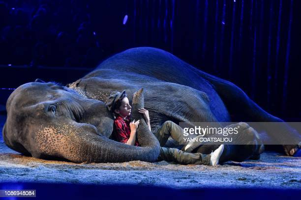 TOPSHOT A member of the Gartner's training elephants family holds the trunk of an elephant as he performs during the gala of the 43th MonteCarlo...