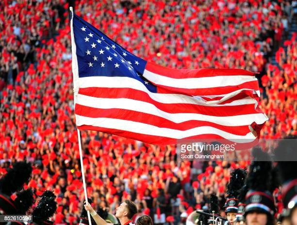 A member of the Georgia Bulldogs Cheerleaders takes the American flag to midfield as the team is introduced before the game against the Mississippi...