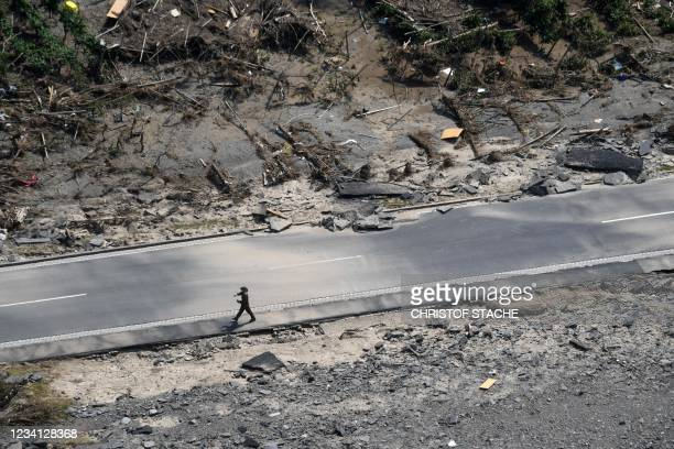 Member of the German armed forces Bundeswehr walks along the destroyed B267 federal highway between Rech and Mayschoss, near the municipality of...
