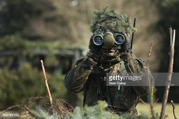 A member of the German Bundeswehr's 371st Armoured Infantry Battalion looks through binoculaurs during a media event at the battalion's base on March...
