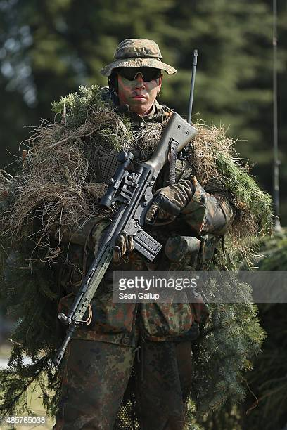 A member of the German Bundeswehr's 371st Armoured Infantry Battalion stands in camouflage with a sniper rifle during a media event at the...