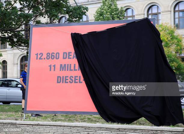 A member of the German Environmental Action places a big banner with black outer cover in front of the Ministry of Transportation building to protest...