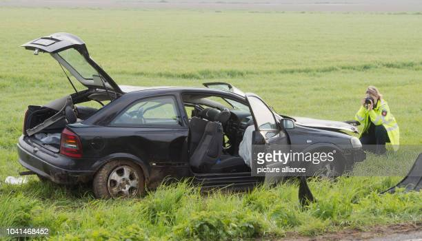 VICTIM A member of the German police secures traces next to a car wreck on a field next to a road between Hiddestorf and Pattensen Germany 01 May...