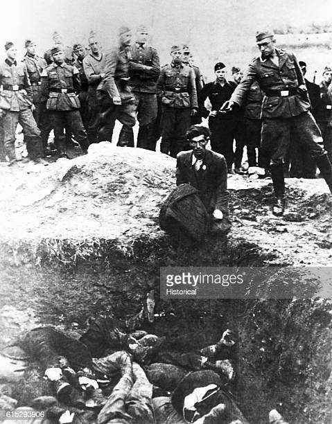 A member of the German S S Einsatz Gruppen D prepares to shoot a Polish Jew who is kneeling on the edge of a mass grave almost filled with previous...