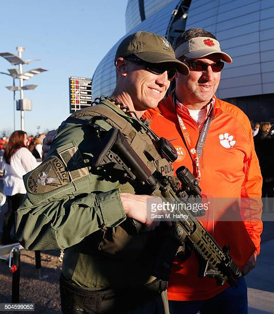 A member of the Glendale Police Department's Special Weapons and Tactics patrol the exteiror of the stadium prioir to the 2016 College Football...