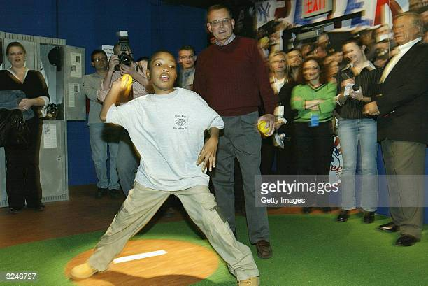 A member of the Gloria Wise Boys And Girls Club throws a pitch as Don Zomer Derek Jeter's high school coach from Kalamazoo Central High looks on at...