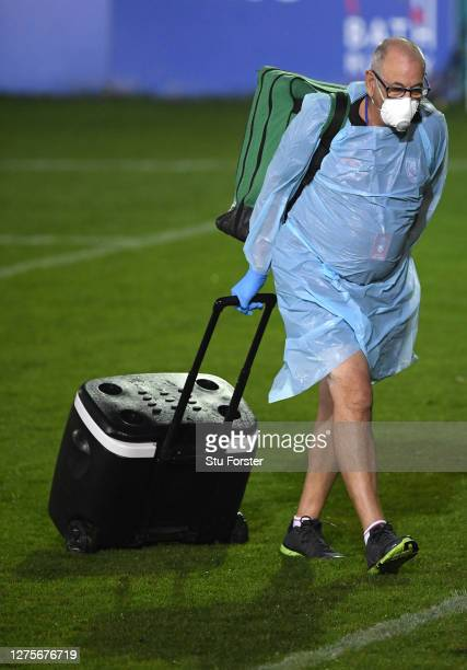 A member of the Gloucester medical staff wearing PPE walks across the pitch after the Gallagher Premiership Rugby match between Bath Rugby and...