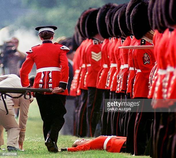 A member of the Governor General's Foot Guards lays on the ground after fainting at a changing of the color ceremony in Ottawa Canada with Queen...