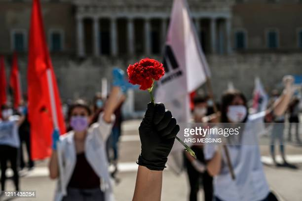 TOPSHOT A member of the Greek Labour Union holds a red carnation during a protest in front of the Greek Parliament during the Labour Day...