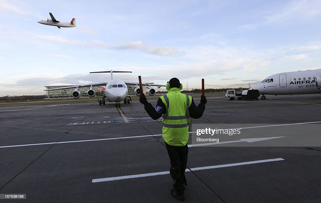 A member of the ground crew directs an Avro RJ85 aircraft, operated by CityJet Ltd., center, into a parking position at City Airport in London, U.K., on Tuesday, Dec. 4, 2012. Air France-KLM Group's CityJet unit is studying options for a new investor, with a trade buyer a possibility given its strength at London City airport, Chief Executive Officer Christine Ourmieres said in an interview. Photographer: Chris Ratcliffe/Bloomberg via Getty Images