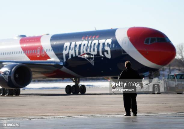 A member of the ground crew guides the team plane of the New England Patriots as it arrives for Super Bowl LII on January 29 2018 at the...