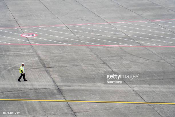 A member of the ground crew walks on the tarmac at Changi Airport in Singapore on Thursday Dec 13 2018 Singapore'sChangiAirport votedtheworld's...