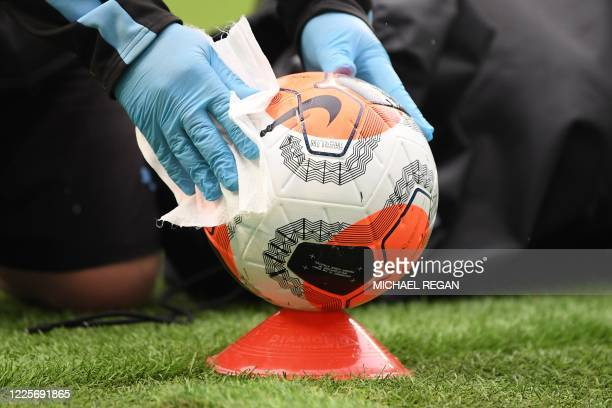 Member of the ground staff cleans a ball before kick off of the English Premier League football match between Manchester City and Newcastle United at...