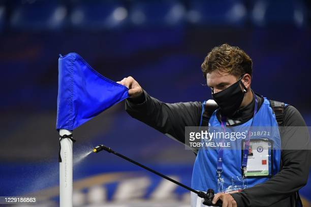 Member of the ground staff disinfects the corner flag ahead of kick off of the UEFA Champions League first round Group E football match between...