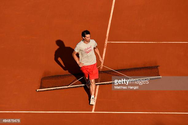A member of the ground staff drags a mat across the clay in between games on day seven of the French Open at Roland Garros on May 31 2014 in Paris...