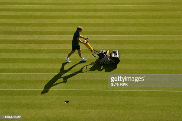 A Member of the ground staff mows the lawn on a court at The All England Tennis Club in Wimbledon southwest London on July 1 ahead of play on the...