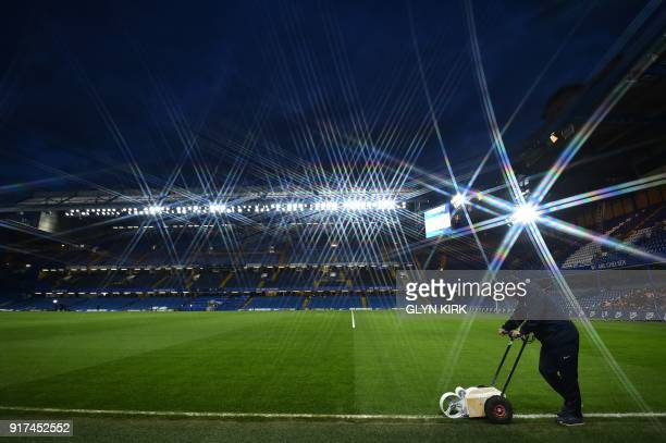 A member of the ground staff paints the white lines on the edge of the pitch ahead of the kick off of the English Premier League football match...